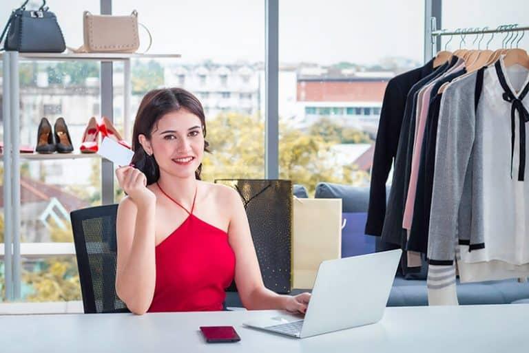 jovem mulher, moça sorridente, com notebook (laptop) vendendo online. E-commerce, loja virtual e negocio online. Dicas para presença digital de pequenos e medios negocios. JR Mídias Sites.